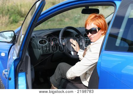 Red-Haired Woman In Sun Glasses In A Blue Car