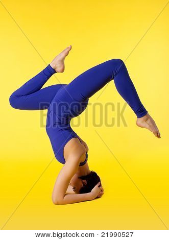 Young woman doing yoga pose - stand on head