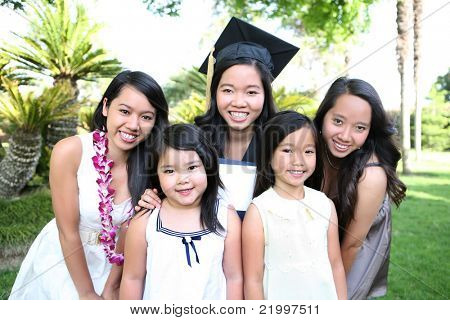 An asian family of girls and sisters celebrating a college graduation