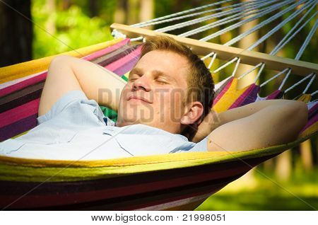 This Young man sleeping in a hammock