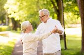 old age, relationship and people concept - happy senior couple dancing waltz at summer park poster