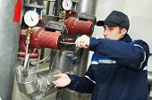 foto of pressure vessel  - maintenance engineer repairing water pump of heating system equipment in a boiler house - JPG