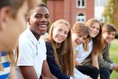 Group Of Teenage Students Sitting Outside School Buildings poster