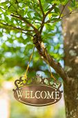 Metal welcome sign hang on tree with bokeh blurred background in the garden poster
