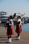 image of bagpiper  - Two bagpipers on a dock with large boats