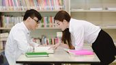 Young students study hard in library. Happy Asian female and male university students doing study re poster