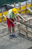 Worker At The Construction Site Making Reinforcement Metal poster