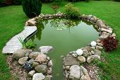 stock photo of fish pond  - Beautiful classical design garden fish pond in a well cared backyard gardening background - JPG