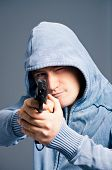 Young man with pistol - studio shot