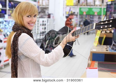Happy girl wearing scarf holds guitar in supermarket; shallow depth of field