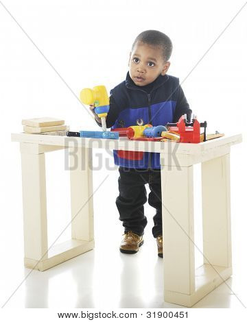 A toddler working with toy tools on a child-sized workbench.  On a white background.