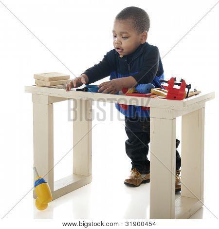 """Uma criança pequena """"carpinteiro"""", reagindo como sua broca cai fora seu banco de ferramenta.  Sobre um fundo branco."""
