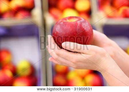 girl hands hold big red apple in shop; shallow depth of field