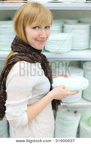 lächelnd mädchen tragen Schal hält einige weißen Platten im Shop; geringe Schärfentiefe