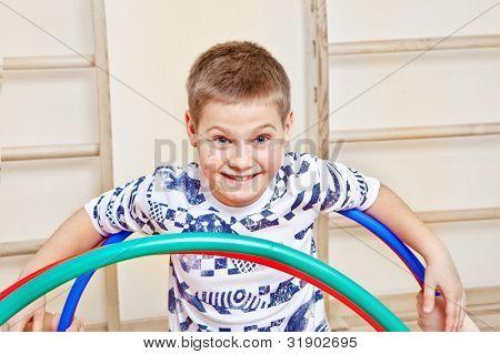 Smiling school aged boy in gym