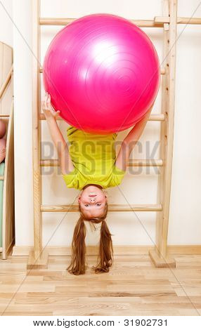 Elementary aged girl hanging on wooden wall bars with a large gymnastic ball
