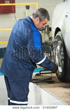 car mechanic installing wheel alignment equipment during suspension adjustment and automobile wheel alignment work at repair service station