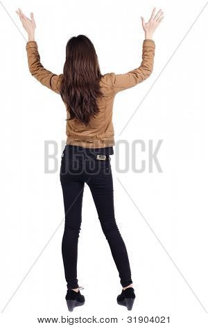 back view of surprised brunette woman with hands up. Girl in jacket. Rear view. Isolated over white