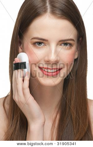 Portrait of young beautiful woman with powder puffs. Pretty woman applying make-up.