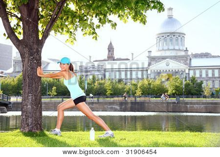 City runner workout woman stretching under tree. Female fitness model training outside on sunny summer day in Montreal Old Port, Montreal, Quebec, Canada. Sporty mixed race Asian / Caucasian girl