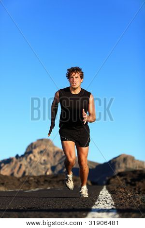 Running - male runner. Man sprinting during outdoor workout training session. Male caucasian athlete running on road in nature.