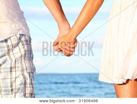 Holding hands couple on beach. Romantic love and happiness concept image with happy young couple. Closeup.