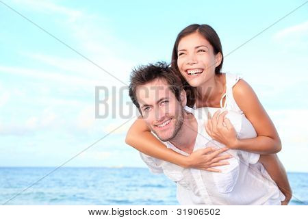 Happy beach couple doing piggyback having summer vacation fun. Young interracial couple, Asian woman, Caucasian man.