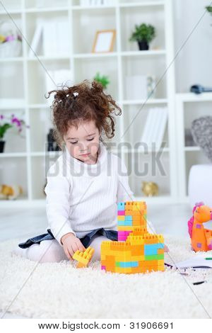 Little girl playing with toys at home