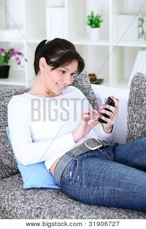 Smiling young woman sending a text message,  lying on a sofa