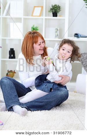 glückliche Mutter und ihrer kleinen Tochter verbringen Zeit miteinander, lachen
