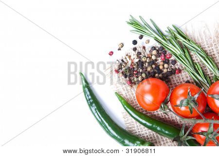 still-life of fresh vegetables and spices over white background.