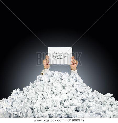 Person unter zerknittertes Stapel von Papier mit der Hand ein Hilfe-Schild