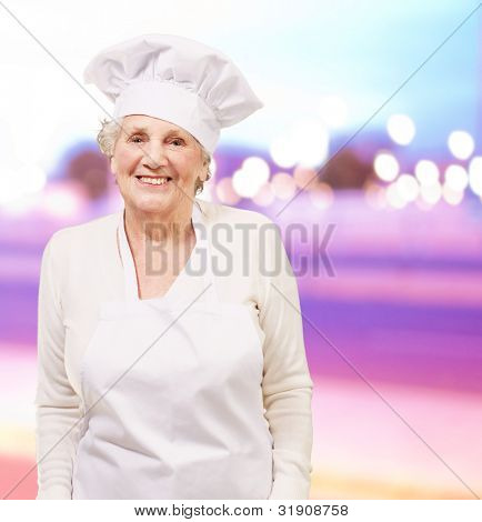 portrait of cook senior woman smiling against a abstract
