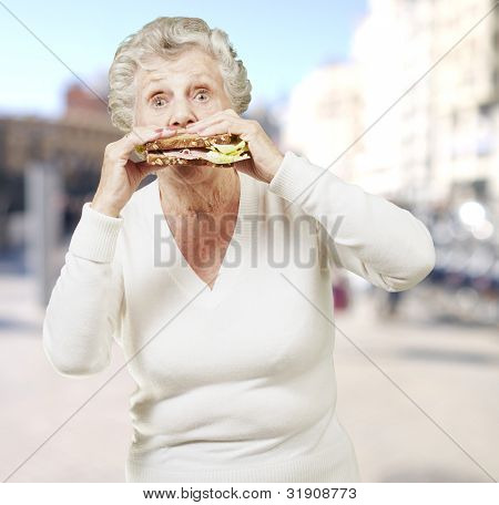 senior woman eating a healthy sandwich against a street background