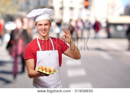 portrait of young cook man holding egg box and doing good gesture at crowded street