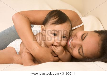 Mother Playing With Her Baby Boy Son On Bed