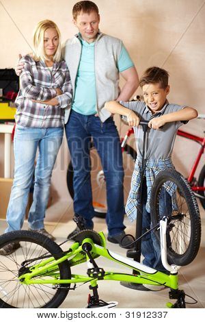 Portrait of cute boy pumping bicycle wheel with his parents on background