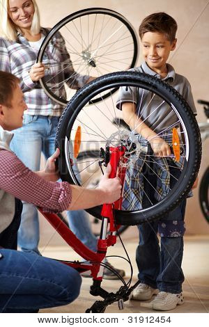 Portrait of cute boy holding bicycle wheel with his father near by