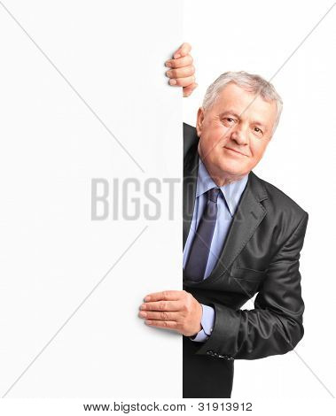 Smiling mature businessman holding a white panel and gesturing isolated on white background