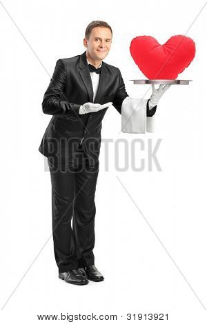 Full length portrait of a butler holding a tray with a red heart shape on it isolated on white background