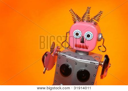 a pink and silver toy maid robot with an orange background