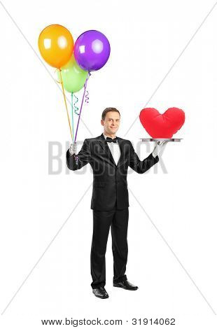 Full length portrait of a butler holding a tray with a red heart shape on it and balloons isolated on white background