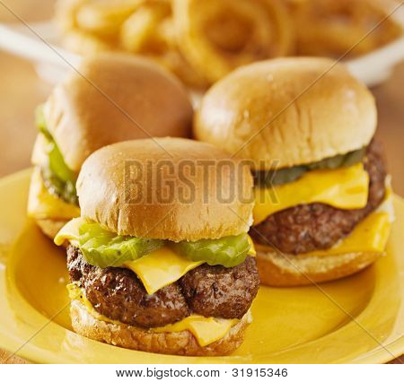 three mini burger sliders with cheese and pickeles.