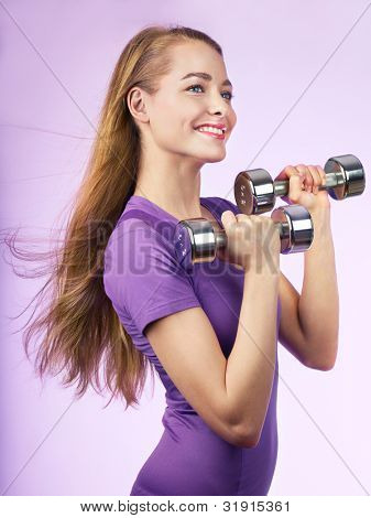 Portrait of smiling young woman with dumbbells