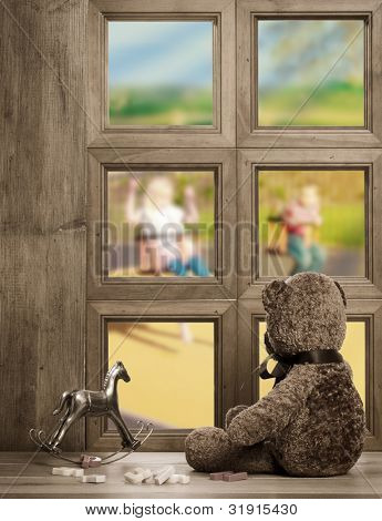 Teddy bear watches from the nursery window - waiting for the return of the children playing on the swings
