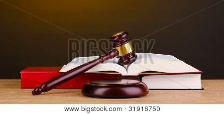 Martelo de juiz e livros sobre a mesa de madeira no fundo marrom
