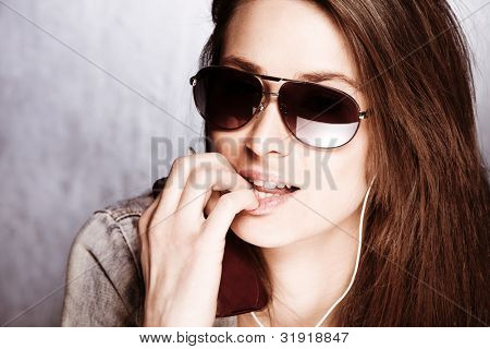 girl with sunglasses earphones and mobile phone in hand, studio shot