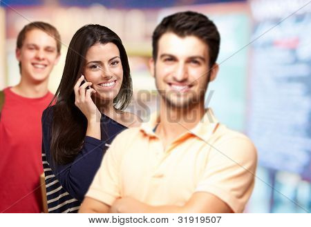 young friends smiling and one girl talking on mobile over abstract background