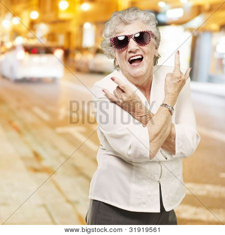 portrait of senior woman doing rock symbol against a city night
