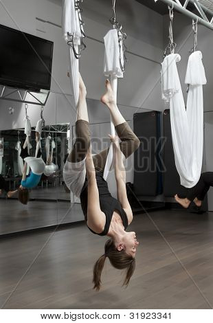 Woman doing anti-gravity exercise in fitness center.